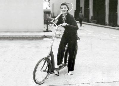 Rita Hayowrth con un patinete de rueda grande