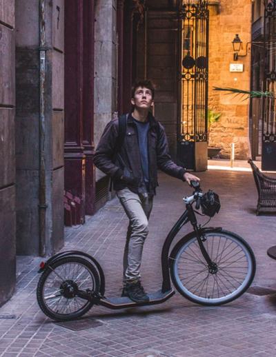 Hombre en la ciudad con el patinete Gravity scooter