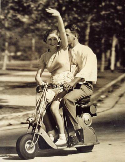 Pareja sobre una moto-scooter de rueda pequeña